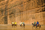 Horseback riders crossing stream below towering sandstone walls near White House Ruin in Canyon De Chelly National Monument, Navajo Nation, Arizona, AGPix_1106