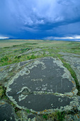 Indian petroglyphs on rock surface with approaching storm over Bear Paw Mountains on the Fort Belknap Indian Reservation, near Harlem, Montana, USA, AGPix_1182
