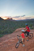 Father and son enjoy sunset view while mountain biking near Bell Rock with Cathedral Rock in distant background, Coconino National Forest, Sedona, Arizona, AGPix_1253