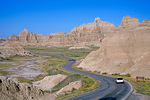 Car driving on park road among Badlands landscape at Badlands National Park, South Dakota, AGPix_1449