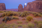 Full moon setting behind sandstone mesa and spires at Monument Valley Navajo Tribal Park, Arizona, AZ_10789,AGPix_1601