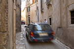 Vehicles drive narrow streets while pedestrian watches traffic among the ancient buildings, in historic town of Amelia, Umbria, Italy, AGPix_1889