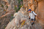 Hiker hanging on to chain on Hidden Canyon Trail at Zion National Park, Utah, AGPix_1918