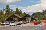 National Park Service Entrance Station at South Rim, cars line up to visit park on busy summer afternoon at Grand Canyon National Park, Arizona, AGPix_1930