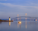 Goat Island lighthouse, lone sailboat moored and Newport Bridge