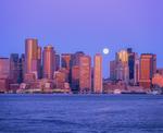 Boston city skyline with setting full moon at dawn
