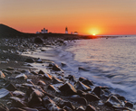 Rocky beach and surf with Point Judith Lighthouse silhouette at sunrise