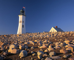 Scituate light and keepers house with pattern of stones on beach