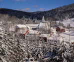 Homes and church surrounder by snow covered trees, hills and fields