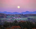 Full moon rises over Jay Peak and hillside farm in fall