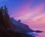 Owl's Head lighthouse and rocky coast line in silhouette at dawn with pink colors in sky