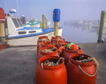 Fishing gear and red barrels, fog, boats at town docks.