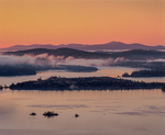 Dawn over Squam Lake, Belknap Mountains, rising fog.