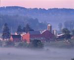 Amish farm on foggy morning, barns and outbuildings.