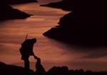 Chukar hunter with dog at sunset above Brownlee Reservoir