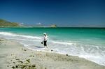 Woman walking on beach along Sea of Cortez near Cabo Pulmo, Mexico