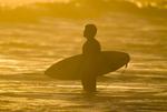 Surfer watching waves at sunset at La Poloma Uruguay