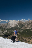 Woman and dogs hiking in a snowbank in the White Cloud Mountains Idaho with Antz Basin and David O. Lee Peak in the background (MR No. AMR_13.01)  (proposed Wilderness Area and currently under consideration for National Monument status -late 2013)