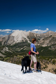 Woman and dogs hiking in a snowbank in the White Cloud Mountains Idaho with Antz Basin and David O. Lee Peak in the background (MR No. AMR_13.01)  (proposed Wilderness Area and currently under consideration for National Monument status - late 2013).