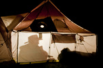 Hunter in cowboy had silhouetted in a wall tent at night in deer hunting camp in Owyhee County Idaho