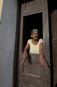 Elderly Cuban woman standing in her doorway in early evening in Trinidad Cuba