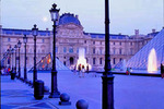A moon rises above the palace, the I. M. Pei Pyramid and the courtyard outside the Louvre Museum.