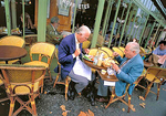 Two elderly gentlemen lunch outside among the autumn leaves at Cafe Pavis on Paris' Left Bank.