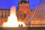 At dusk, a young couple is seated by a reflecting pond and its backlit fountain with the Grand Pyramid and the Louvre spotlit behind them.
