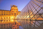 The Louvre's Grand Pyramid and the Richelieu Pavilion reflected in the reflecting pool at night.