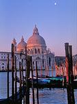 Moored gondolas and a moon over Venice's Salute basilica at sunrise.