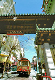 A motorized cable car passes under Chinatown Gate, the entryway to Grant Avenue (and Bush), one of the main thoroughfares in Chinatown.  
