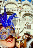 Wearing a Carnival mask, a woman watches the opening day parade for Winter Carnival outside the San Marco Basilica.