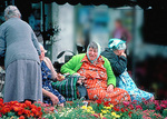 Local women, dressed in bright floral prints, chat on benches by the market at Loches, by the Chateau de Loches, in spring.