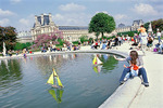 Mother and infant watch toy sailboats float in the Tuileries Garden's reflecting pool, on a fine spring day, during a long holiday weekend in May.