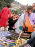 A young boy, holding a launching pole, is very intent, before selecting a sailboat at the rental stand in the Tuileries Gardens, during a holiday weekend in May.