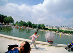 A sun worshipper, a young boy and his stick, and a woman under a parasol -- all enjoy a holiday weekend in May, by the reflecting pool in the Tuileries Gardens.