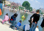Mothers and their children watch toy sailboats float on the reflecting pool of the Tuileries Garden, during a long holiday weekend in May.