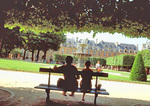 A young couple sit on a bench under the cool shade of chestnut trees, in spring, enjoying a view of the fountain in Place des Vosges, the oldest square in Paris, in the Marais.