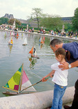 Father and young daughter launch a toy sailboat in the reflecting pool of the Tuileries Garden, during a spring day in May.