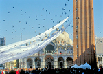 A diaphanous drape extends past the Doge's Palace, while pigeons soar above the crowds in Piazza San Marco, during Winter Carnival.