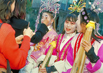Young Chinese-American women, dressed in costume, have their makeup applied before the Chinese New Year Parade.