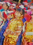A young Chinese-American girl, dressed in a bright yellow costume, quietly awaits the beginning of the Chinese New Year Parade.