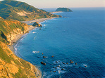 Green ridges and crystal-blue waters of the rugged Big Sur coastline, along Highway 1, at sunset.