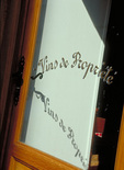 """""""Quality wines"""" - French lettering on a cafe door in Paris."""