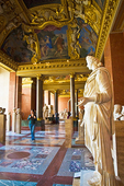 A woman walks among Roman statues in the Louvre's lavishly-decorated Salle des Saisons.