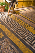 A fashionably-dressed shopper walks on the restored mosaic floor of the Galerie Vivienne.