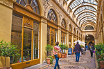 Shoppers walk under the iron and glass arcade of the 19C Galerie Vivienne.