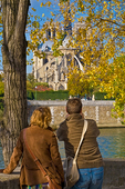 A young couple photograph Notre Dame Cathedral from a quai on Ile St-Louis.