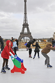 A young ice skater serenely maintains her balance while others falter; Paris' Trocadero Ice Rink with the Eiffel Tower as a backdrop.