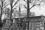 A bookseller chats quietly with an old friend in the winter light; Notre Dame Cathedral is in the background.